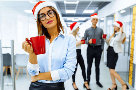 Happy young business woman in Santa Claus hat, holding a red mug, with a group of colleagues in the background, during a coffee break in the office. Meeting new year and christmas