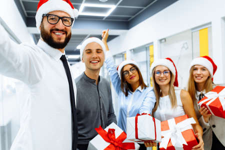 Happy group of businessmen in Santa Claus hats, with Christmas gifts are having fun celebrating New Year and taking selfie on a mobile phone