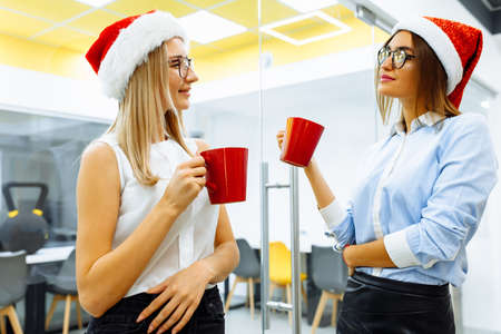 young business women in santa claus hats drinking tea or coffee during office break