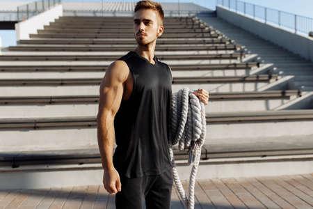 222e, .m1.22ьььььь7wap tzhzhzh / tt / zzh / b Sporty young man doing fitness workout outdoors, muscular man using two fighting ropes, sport, motivation Reklamní fotografie