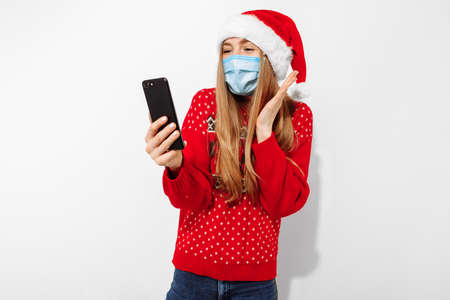 Young happy woman in a red Santa Claus hat and a medical mask on her face, waving, making a video call on a smartphone on Christmas eve, on a white background