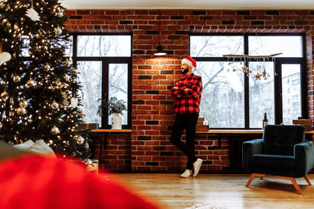 Smiling Christmas Man Wearing Santa Claus Hat Celebrating Christmas At Home Near Christmas Tree, Merry Christmas