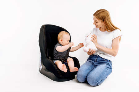 Mom with baby in a store buys a car seat, on an isolated white background Standard-Bild