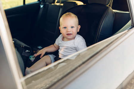 A small child is fastened with a seat belt on the car safety seat