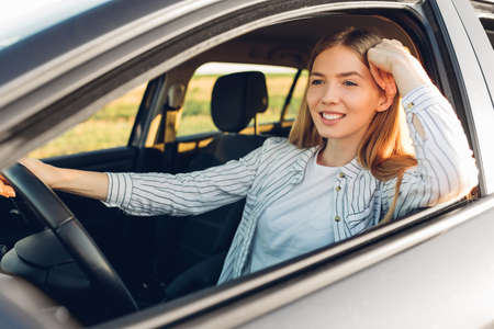 Beautiful young happy smiling woman driving her new car at sunset Archivio Fotografico