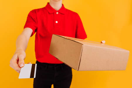 Happy young woman courier, in red uniform, delivery officer holding cardboard box and credit card on isolated yellow background