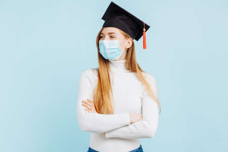 Happy thinking graduate in medical mask, student in graduation hat with briefcase thinks and looks to the side on blue background