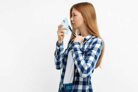 Sick young female patient wearing oxygen mask on isolated white background