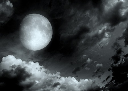 The moon in the night sky in clouds 写真素材