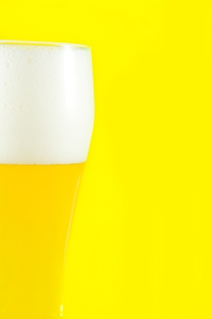 Glass of beer with foam on yellow background Stock Photo - 9572848