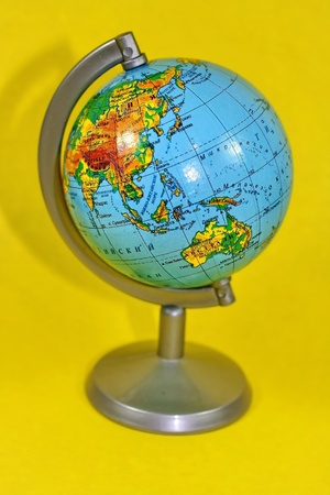 The small colourful globe is isolated on a yellow background photo