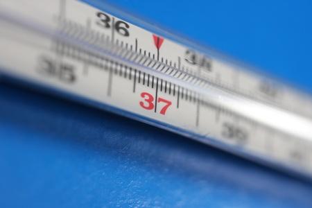 chorowity: Medical termometr na niebieskim tle. Temperatura 37.