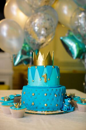 1 year birthday cake in blue with a gold crown