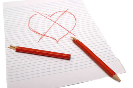 Crossed heart with a broken pencil on paper. White background Stock Photo