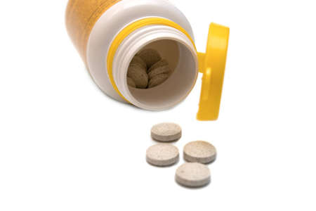 Pills spilling out of a prescription bottle on white background