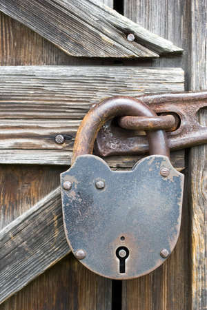 Old locked padlock on the wooden door Stock Photo - 7309295