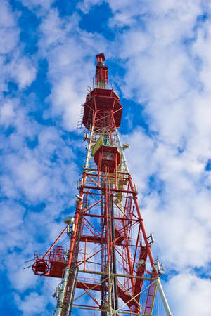 Radio communications tower with dishes against a blue sky