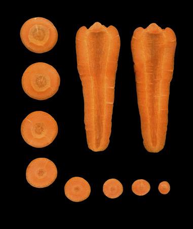 zanahoria: Las verduras frescas - zanahorias cortadas en trozos sobre un fondo negro. Secciones transversales y longitudinales de zanahoria natural, sobre un fondo negro. Foto de archivo