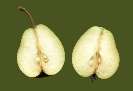 Two halves of one fruit pears isolated on a green background. Longitudinal section fruit pears, where you can see his heart.