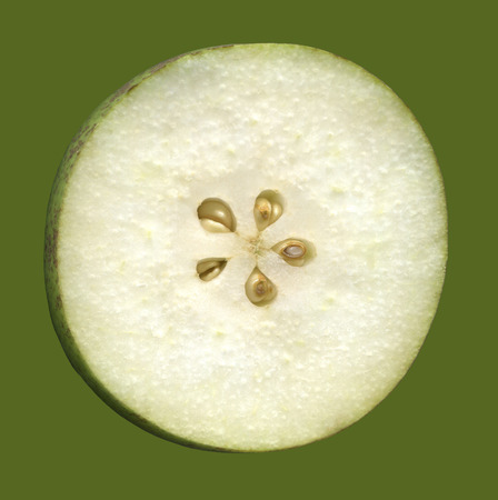 Cross section of fruit of pear, isolated on a green background. Building pear from the inside, where you can see her flesh and the core with the seeds.