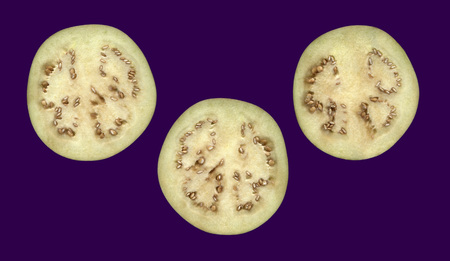 Eggplant in cross section.Three slices of eggplant isolated on a dark background Banque d'images