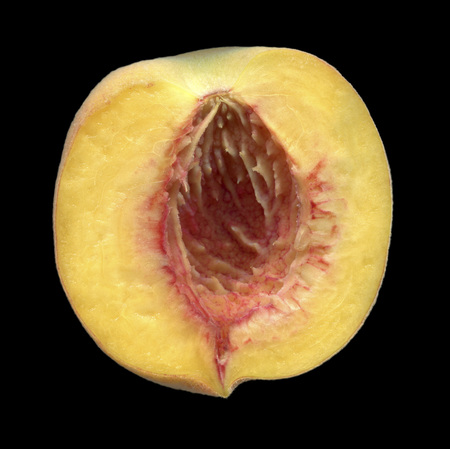Half of ripe peach, pitted.A slice of peach, isolated on black background