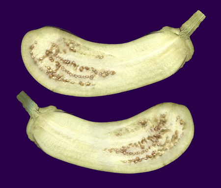 Eggplant in a longitudinal section.Two halves of the eggplant isolated on a dark background