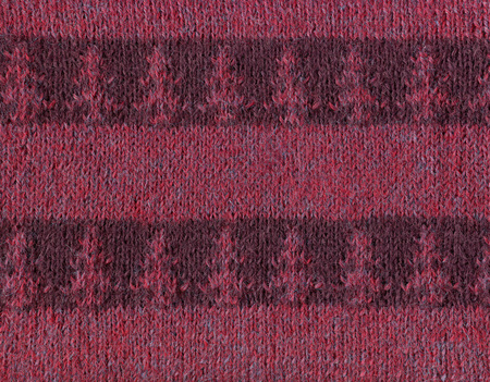 Striped knitted fabric with a pattern of fir trees.Decorative material, background, texture, wallpaper