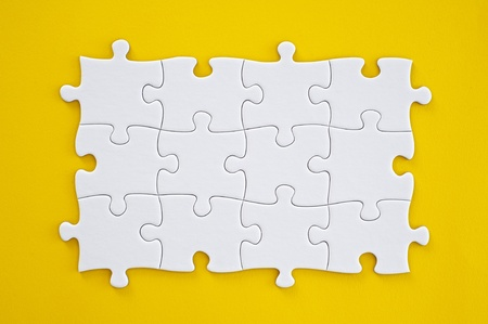 Connected blank puzzle pieces isolated on a yellow background  photo