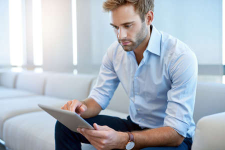 Handsome and stylish young man sitting on a modern couch and using a digital tablet