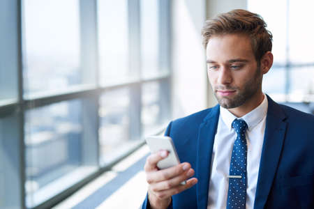 Stylish young businessman standing in a bright modern office with large windows, looking at the screen of his mobile phone