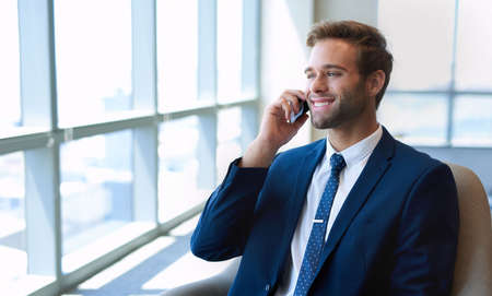 Handsome young executive in a corporate suit and tie, talking on his mobile phone and smiling while looking out of the large windows of a modern office space