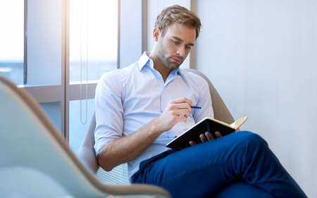 Young businessman with stylish hair and clothing, sitting next to a large window and thinking while writing in his journal