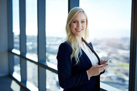 Portrait of a smiling young businesswoman holding a cellphone while standing by windows overlooking the city in a modern office building