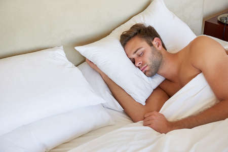 Handsome young man sleeping deeply on a comfortable pillow in a double bed with clean linen and soft pillows Standard-Bild