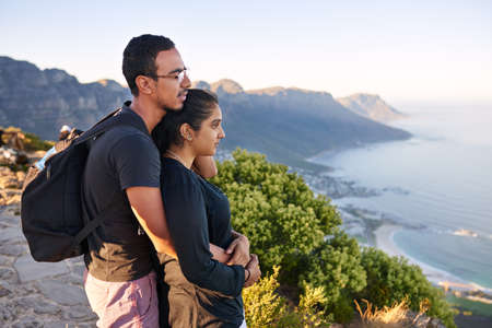 Loving young Indian couple taking in the view while on a mountain nature hike