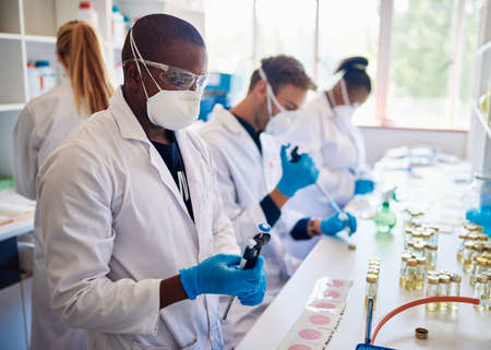 Group of diverse technicians wearing face masks and coats working together with samples at a table in a lab