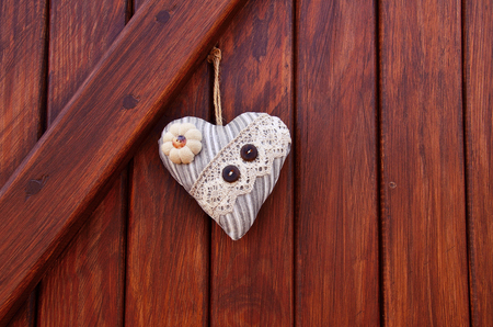 textile heart with lace and two button on the wood wall