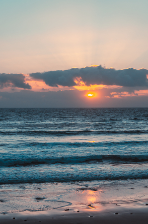 ocean landscape with sand beach and wave  at yellow and pink  sunset Fuerteventura. Stock Photo
