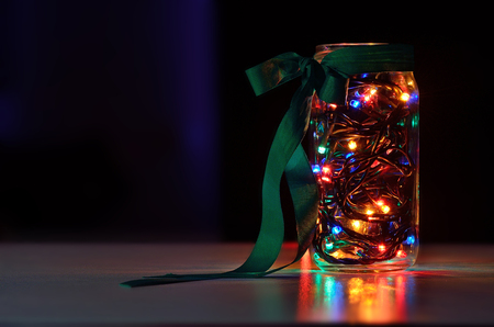 garland in the jar with colorfull ligh on the black background 스톡 콘텐츠