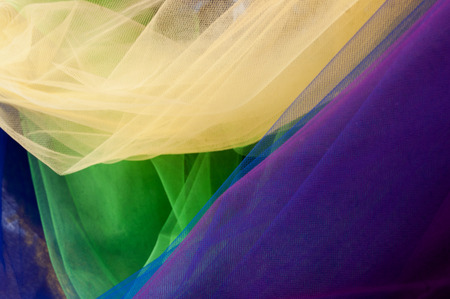 downwards: Cloth Yellow and green blue purple cloth draping downwards.  Closeup picture.  This picture was taken at the San Francisco pride Stock Photo