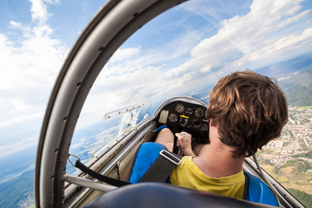 pilot: pilot in the cockpit of an aircraft which flies over the landscape