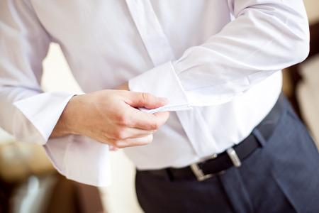 bata blanca: a man fastening a cuff - before getting married