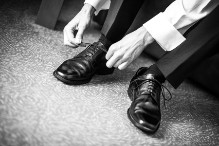 agrees: groom agrees shoes on wedding day, Business man dressing up with classic, elegant shoes Stock Photo