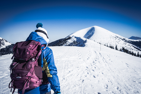 Young woman walking on snowy European mountains