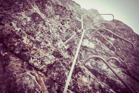 Climbing wall in Italy, Detail of ferrata climbing, Via Ferrata in mountains in summer, Via ferrata in mountains, Symbol of mountain climbing, Belaying rope on via ferrata