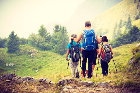 Active seniors on a trip in mountains, Group of tourists living in a healthy lifestyle enjoying nature in Italy, Summer walk in nature, Tourists on oor of rods