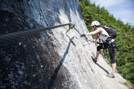 Symbol of climbing on ferrata, Belay rope on via ferrata, Raised steel rope with climber, Belaying on rock for climbers