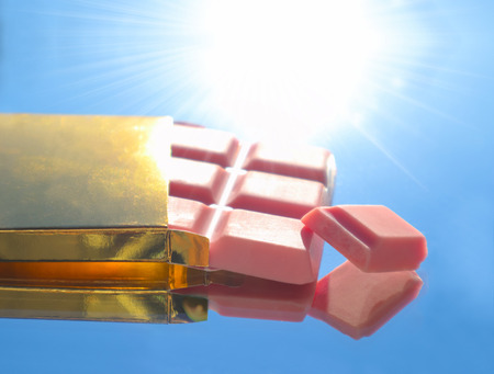 Pink chocolate bar in golden shiny box. Vivid image of luxury candy dessert on the sunlight.