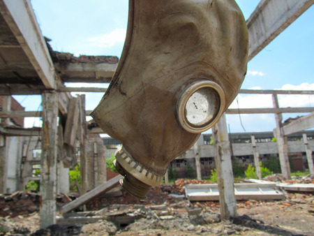 Old broken gas mask and destroyed abandoned industrial building. Dirty protection equipment for a post apocalyptic concept.